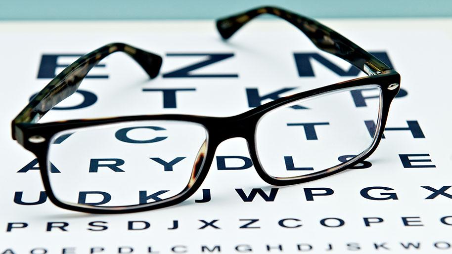 Brown glasses sitting on an eye chart