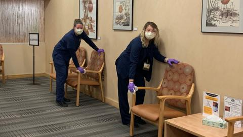 Two staff members disinfecting a clinic waiting room at the Kellogg Eye Center